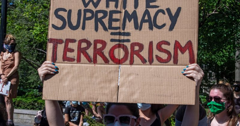 """Student holding a sign reading """"White Supremacy = Terrorism."""""""